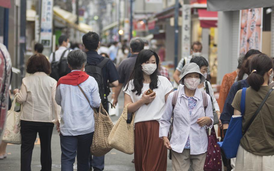 People wear masks while walking near Ofuna Station in Yokohama, Japan, July 29, 2020.