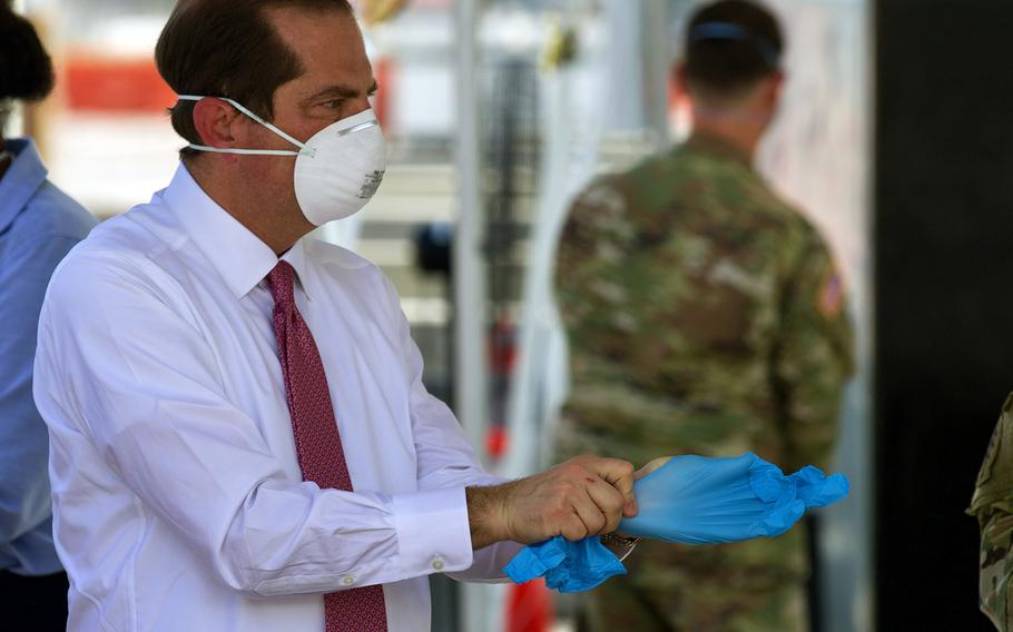 Secretary of Health and Human Services Alex Azar puts on protective equipment before joining the Florida National Guard for a tour of a coronavirus-testing site in Jacksonville, Fla., May 22, 2020.