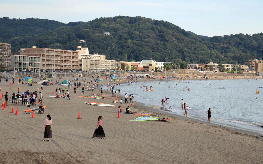 People, some wearing masks to protect against the coronavirus, hang out at a beach in Hayama, Japan, Thursday, Aug. 13, 2020.