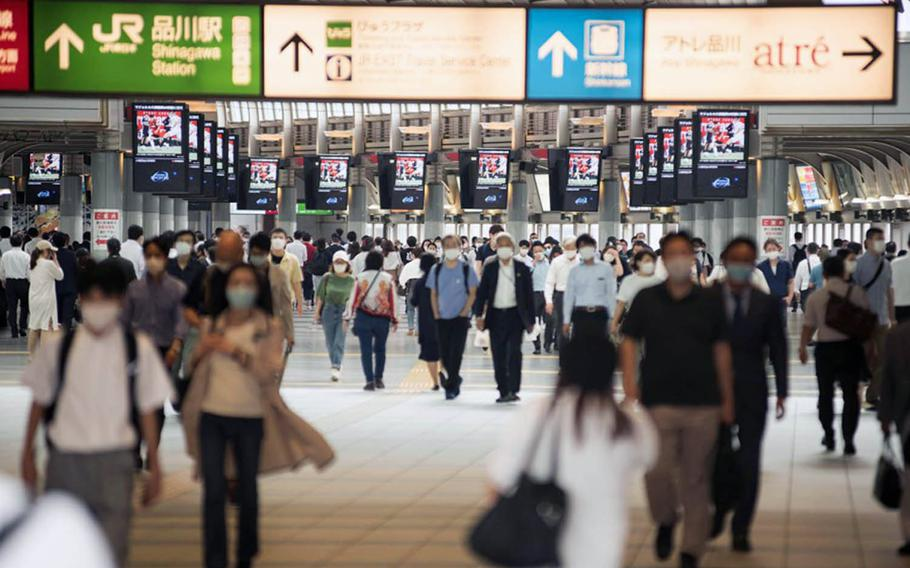 Commuters wear masks as they traverse Shinagawa Station in central Tokyo, July 13, 2020.