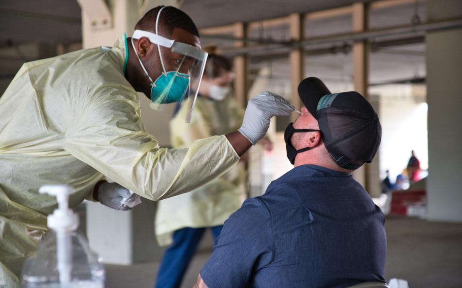 Staff Sgt. Lamaar Melvin of the 51st Medical Operations Squadron administers a coronavirus test at Osan Air Base, South Korea, July 14, 2020.
