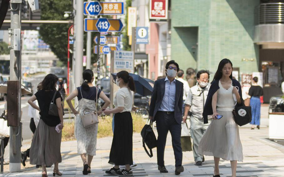People stroll through the Omotesando district of central Tokyo, Aug. 14, 2020.