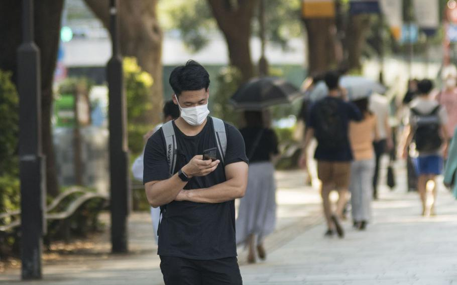 A man stops to check is smartphone in the Omotesando area of central Tokyo, Aug. 14, 2020.