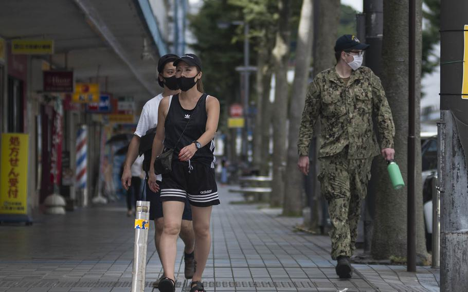 A U.S. Navy sailor and locals wear masks as they stroll down a walkway in Yokosuka, Japan, Thursday, Aug. 27, 2020.