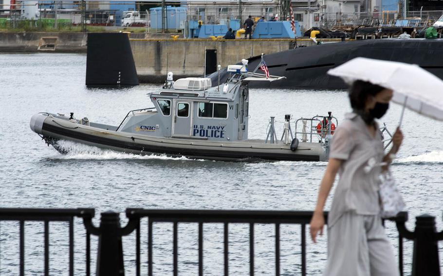 A woman walks by a U.S. Navy police boat patrolling near Yokosuka Naval Base, Japan, Aug. 27, 2020.