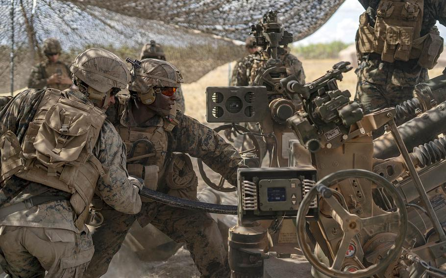 Cpl. Trey Teal and Lance Cpl. Andre Fair of the Marine Rotational Force — Darwin ground-combat element, prepare for a fire mission at Mount Bundey Training Area, Australia, Aug. 6, 2020.