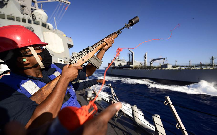 U.S. Navy Gunner's Mate Seaman Apprentice Isaiah Moore fires the shot line as the guided-missile destroyer USS Chung-Hoon conducts a replenishment-at-sea with the HMAS Sirius during the Rim of the Pacific exercise near Hawaii, Aug. 25, 2020. Devin Langer/U.S. Navy