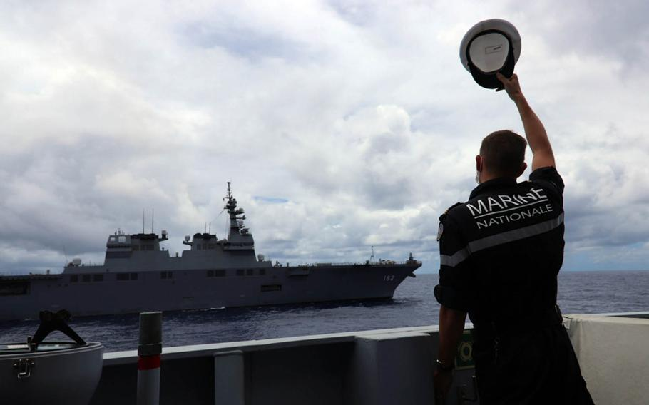 A sailor aboard the French naval vessel FS Bougainville waves as Japan Maritime Self-Defense Force ship JS Ise sails by Aug. 24, 2020, during the Rim of the Pacific exercise held in waters near the Hawaiian Islands. French Navy