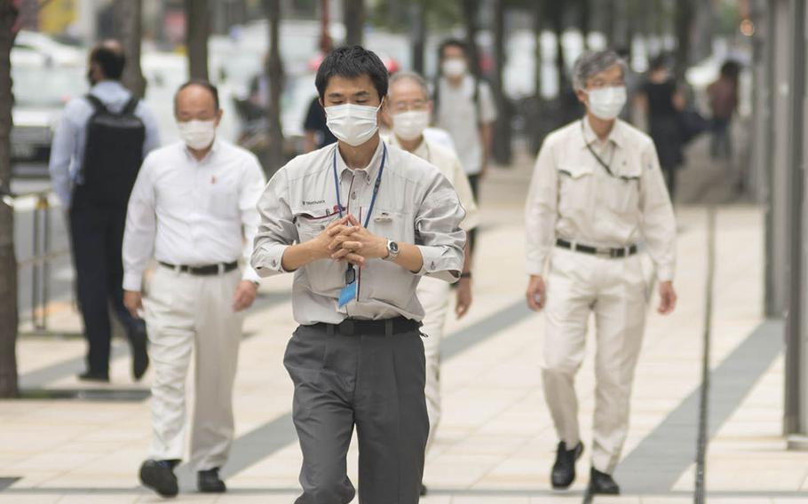 Mask-wearing pedestrians walk down a street on a recent afternoon in the Roppongi district of central Tokyo.