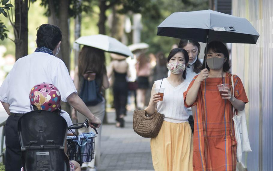 People wear masks to guard against the coroanvirus during a recent afternoon in the Omotesando distrcit of central Tokyo.