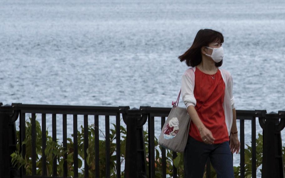 A woman wears a mask to protect against the coronavirus while taking a walk near Yokosuka Naval Base, Japan, Aug. 27, 2020.