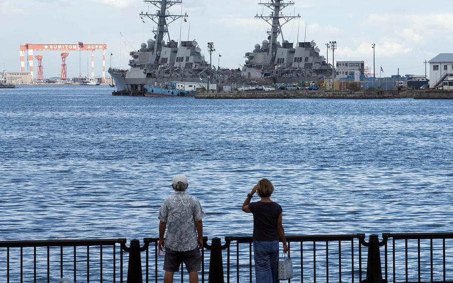 People check out a pair of warships docked at Yokosuka Naval Base, Japan, Aug. 27, 2020.