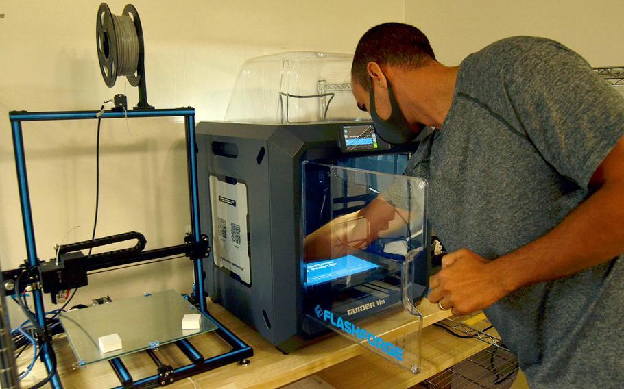 The chief technology officer for YokoWerx, Air Force Master Sgt. Ken Martin, demonstrates the innovation lab's 3D printer at Yokota Air Base, Japan, Sept. 25, 2020.