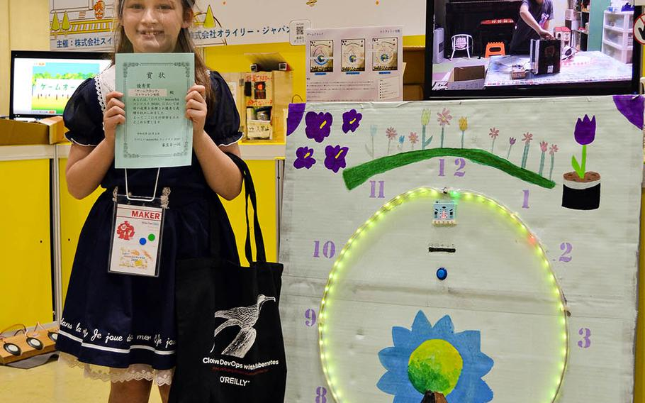 Alice Stratton, a fourth-grader at Daihachi Elementary School near Yokota Air Base, Japan, poses beside her invention, an LED game clock, during Maker Faire 2020 in Tokyo, Saturday, Oct. 3, 2020.