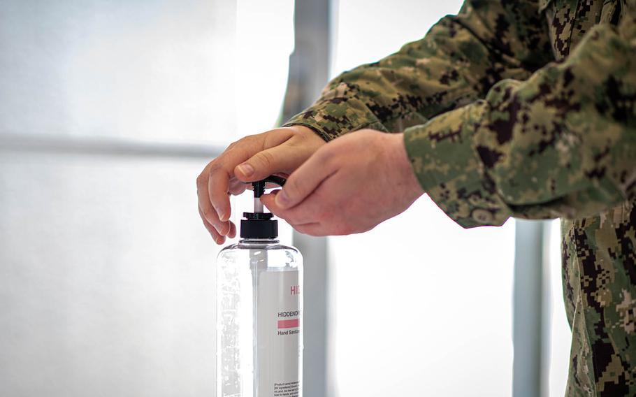 A sailor sanitizes his hands before entering the exchange at Yokosuka Naval Base, Japan, Aug. 13, 2020.