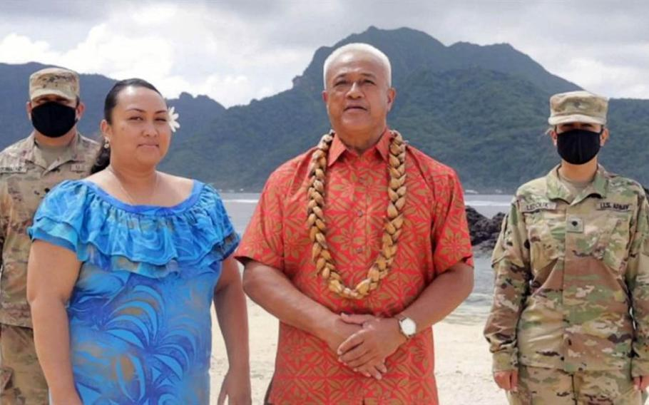 In this image from video, two soldiers stand at attention as Aliitama Sotoa, chairman of the American Samoa Democratic Party, in orange, casts the territory's 11 votes for Joe Biden in a brief segment of the Democratic National Convention on Aug. 8, 2020.