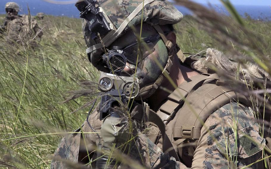 A Marine scans for enemy troops after taking over the airfield at Ie Shima, Okinawa, during Noble Fury drills Wednesday, Oct. 7, 2020.
