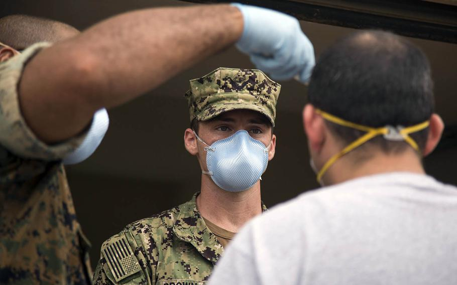 A sailor from the USS Theodore Roosvelt is screened for coronavirus symptoms at Naval Base Guam, May 7, 2020.