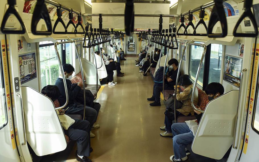 Passengers ride an Ome line train near Yokota Air Base, Japan, Thursday, Oct. 22, 2020.