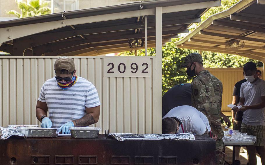 A volunteer prepares food during a barbecue for single service members under quarantine at Yokota Air Base, Japan, Sept. 4, 2020.