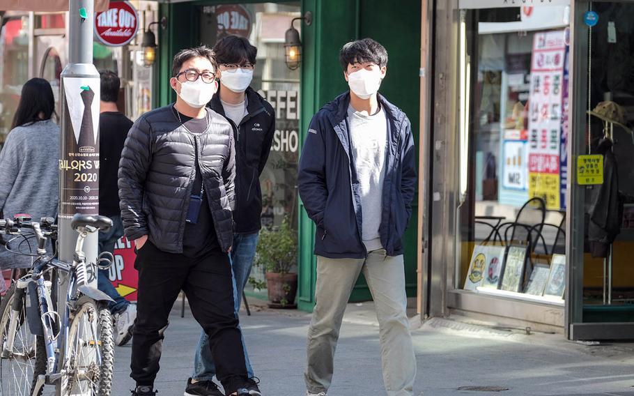 Pedestrians wear masks to guard against the spread of the coronavirus outside Osan Air Base, South Korea, Oct. 20, 2020.