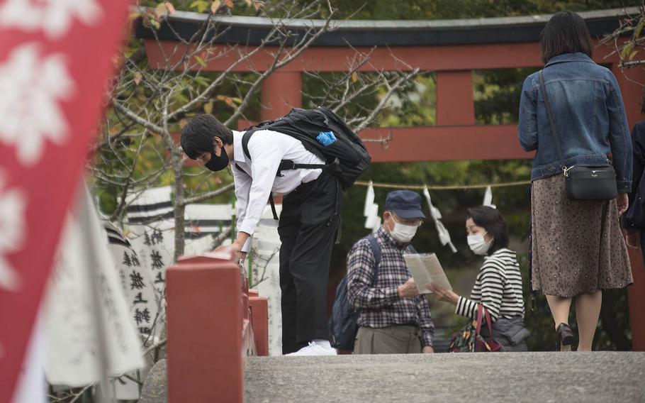 People wear masks to guard against the coronavirus while visiting Kamakura in Kanagawa prefecture, Japan, Oct. 23, 2020.