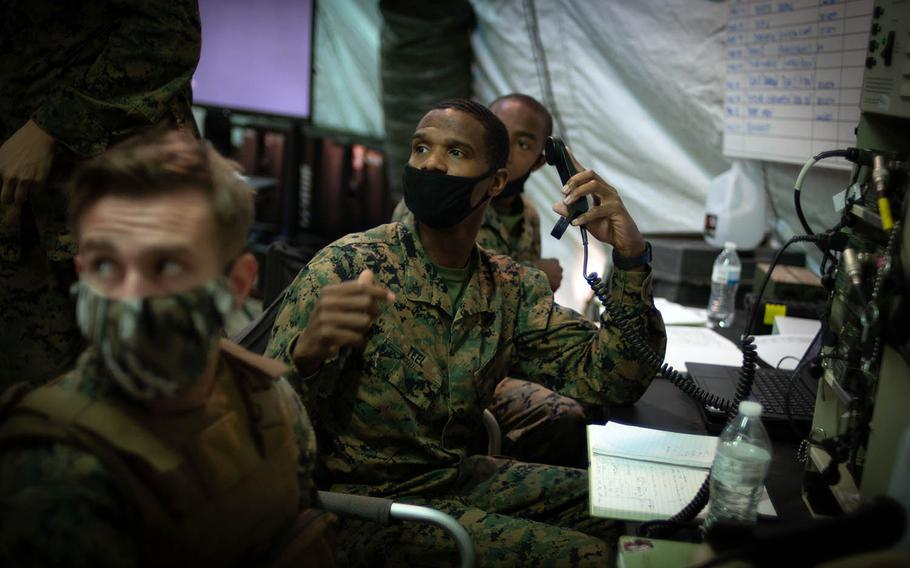 Cpl. William Teel, a radio operator with Marine Wing Support Squadron 171, passes information to his staff sergeant during the Active Shield exercise at Marine Corps Air Station Iwakuni, Japan, Oct. 28, 2020.