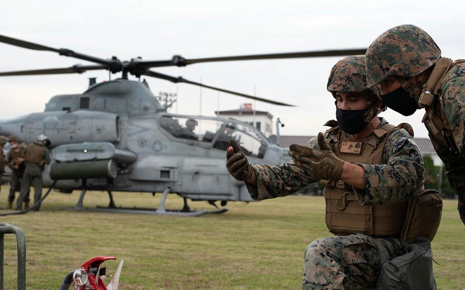Sgt. Isiah Jakes of Marine Wing Support Squadron 171 takes part in a refueling operation for an AH-1 Cobra during an Active Shield drill at Marine Corps Air Station Iwakuni, Japan, Oct. 28, 2020.