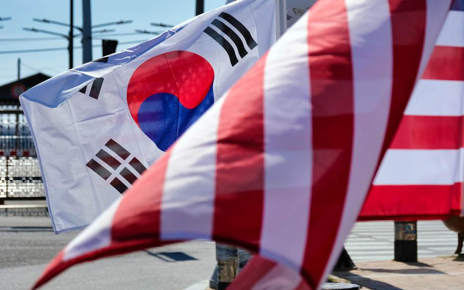 U.S. and South Korean flags flap in the wind outside Camp Humphreys, South Korea, March 16, 2020.