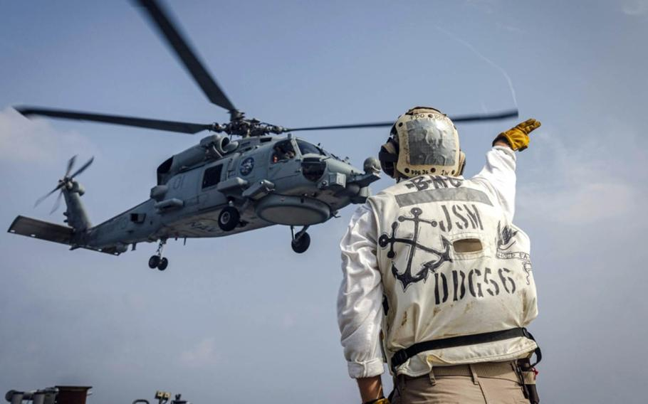A Royal Australian Navy MH-60R Seahawk helicopter takes off from the guided-missile destroyer USS John S. McCain during Malabar drills in the Bay of Bengal, Tuesday, Nov. 3, 2020.