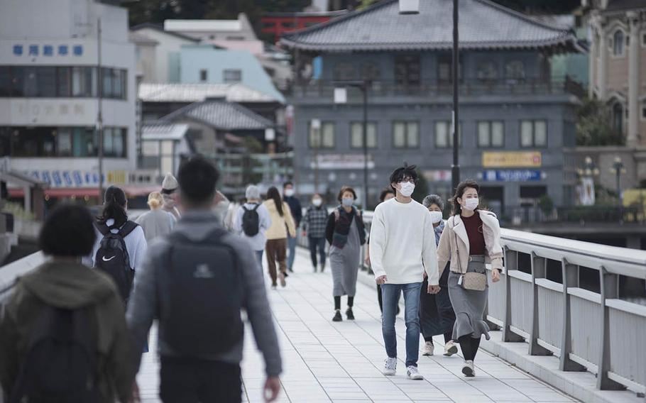Tourists wear masks as they cross a bridge near Enoshima, Japan, Friday, Oct. 30, 2020.