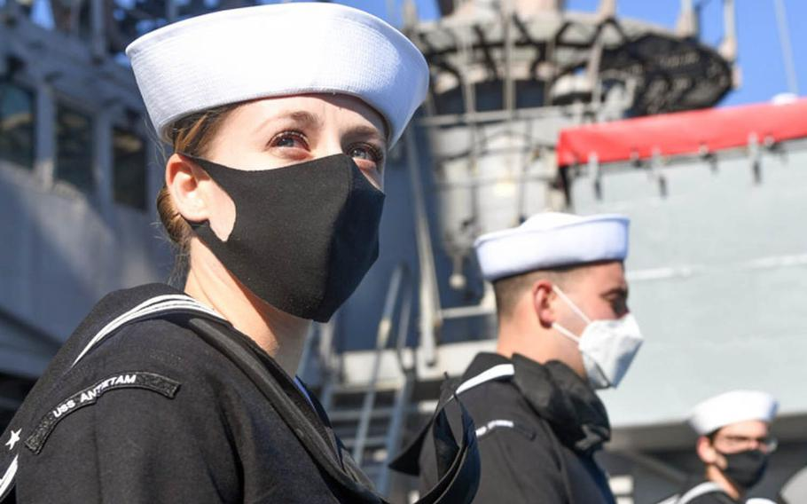 Petty Officer 1st Class Brittany Britos and other sailors man the rails as the guided-missile cruiser USS Antietam returns to Yokosuka Naval Base, Japan, after a nine-month deployment, Tuesday, Nov. 10, 2020.
