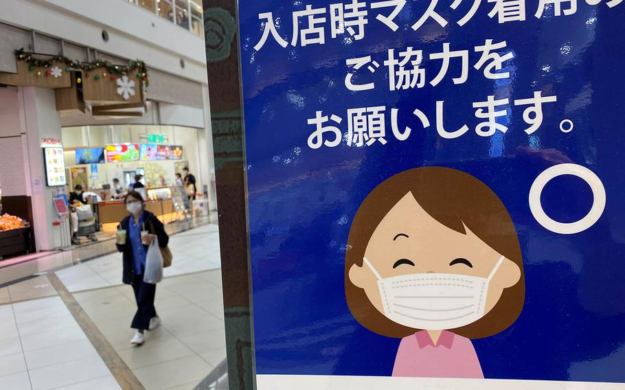 A sign reminds shoppers to wear a mask inside a mall in western Tokyo, Sunday, Nov. 8, 2020.