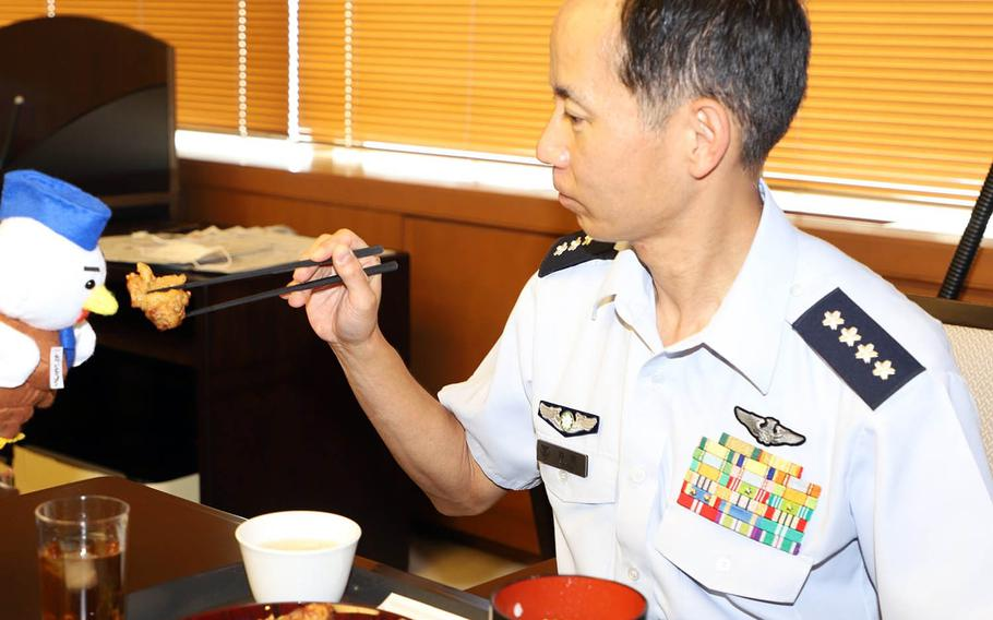 Gen. Shunji Izutsu, chief of staff for the Japan Air Self-Defense Force, pretends to feed fried chicken to the service's mascot in this undated photo.