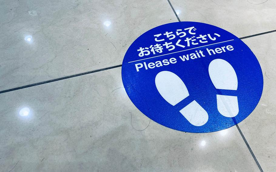 A floor decal reminds patrons to practice social distancing at a shopping mall in western Tokyo, Sunday, Nov. 8, 2020.