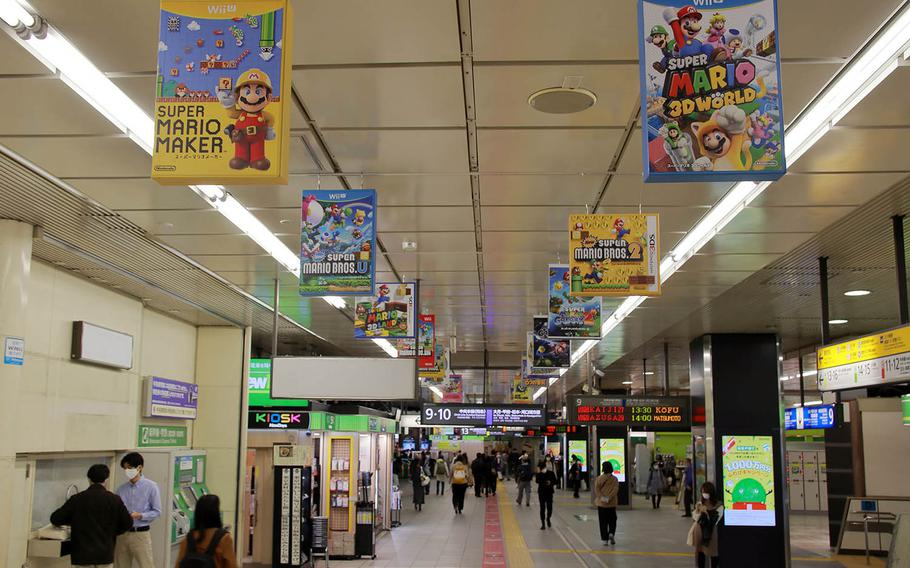 An oversized box-art exhibit chronicles the history of the Super Mario Bros. video game franchise at Shinjuku Station in Tokyo, Nov. 4, 2020.