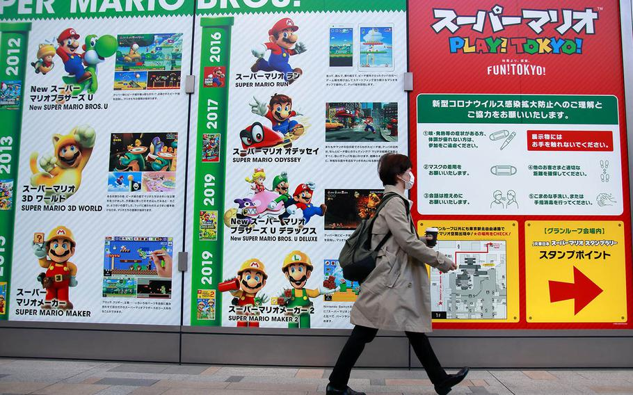A woman walks past a Tokyo Station exhibit celebrating the 35th anniversary of the Super Mario Bros. video game franchise, Nov. 4, 2020.