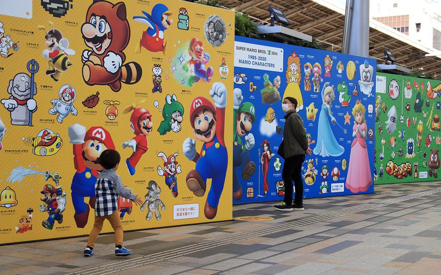 People check out Tokyo Station murals celebrating the 35th anniversary of the Super Mario Bros. video game franchise, Nov. 4, 2020.