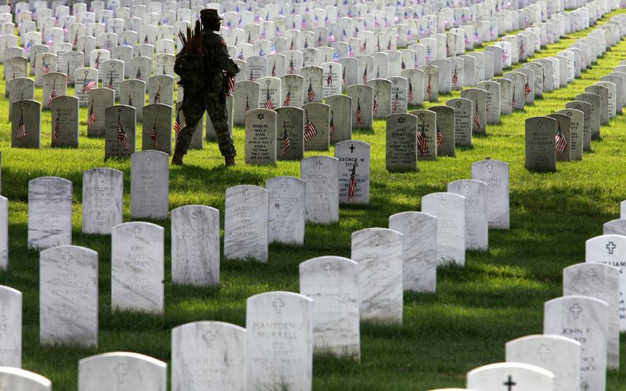 Army 1st Sgt. Shelly Jenkins, with the 3rd U.S. Infantry Regiment known as The Old Guard, places flags on the graves at Arlington National Cemetery in preparation for Memorial Day 2010.