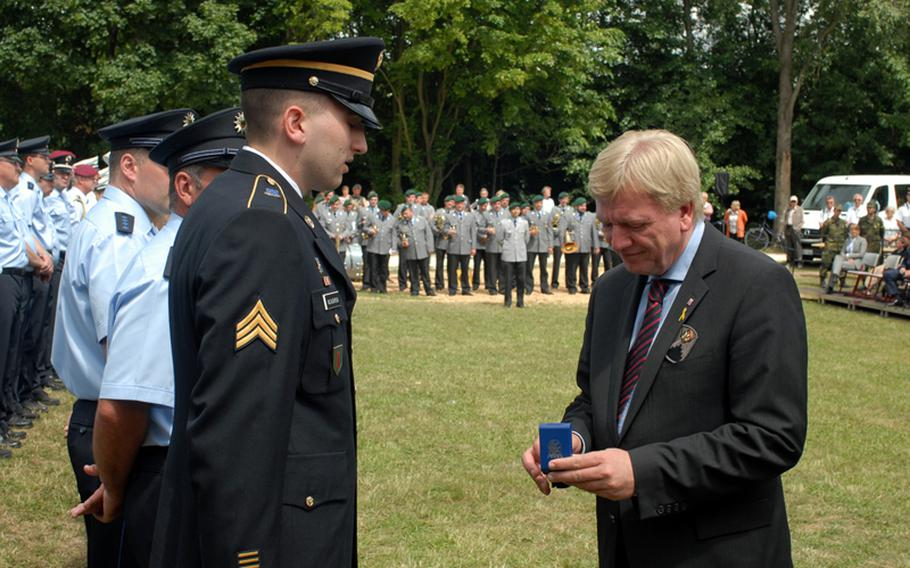 Sgt. John McCaughrean listens to Hessen Minister President, Volker Bouffier, before being presented with the German state's medal for civil courage.  In front of hundreds of spectators at this year's Hessentag festival in Oberursel, it was a thankful German government that recognized Sgt. John McCaughrean for coming to the aid of wounded victims of a serious car accident and helping to nab two men who tried to flee the scene.