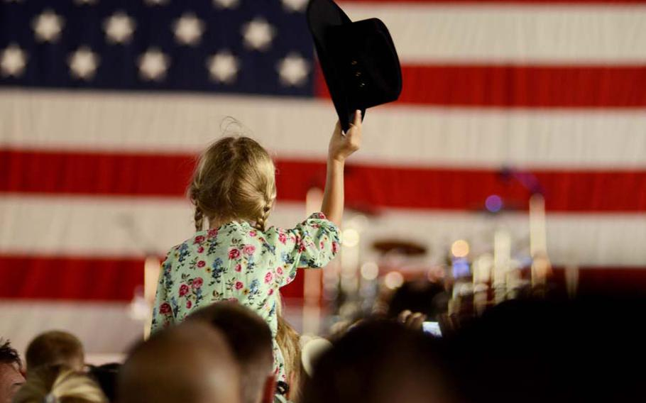 Annabella Seidl, 6, waves her cowgirl hat before country music star Trace Adkins came on stage. Adkins performed on Ramstein Air Base Sunday to commemorate the 10th anniversary of 9/11. The free concert, sponsored by the United Services Organization, was held in a hangar on base.