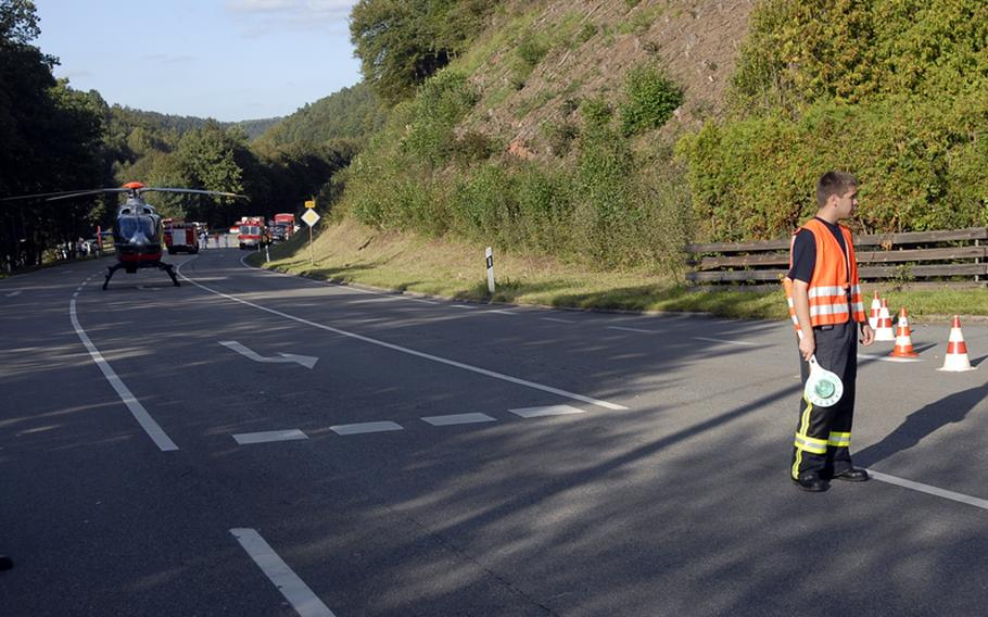 Pascal Zirkel, a German firefighter with the village of Krickenbach, helps block traffic on highway B-270 outside the entrance to the village of Schopp on Wednesday, after what's believed to be a World War II-era phosphorous bomb was discovered behind the Schopp train station, according to local firefighters at the scene.