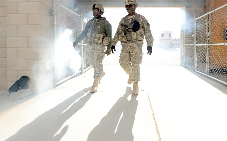 Pfc. Damien Davis, left, and Staff Sgt. James Bates, both of the Operations Group at the National Training Center in Fort Irwin, Calif., walk through a entryway obscured by smoke, Feb. 20, 2013. Their group is documenting the  2nd Brigade Combat Team, 1st Infantry Division from Fort Riley, Kansas as they train at NTC as the first brigade to be aligned with AFRICOM.