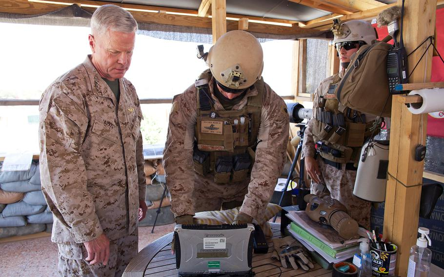 Gen. James F. Amos, commandant of the Marine Corps, reviews equipment with a Marine during a visit to the U.S. Embassy compound in Tripoli, Libya, on June 16, 2013.