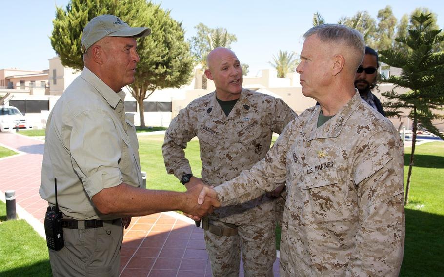 Gen. James F. Amos, commandant of the Marine Corps, greets a civilian worker as Sgt. Maj. of the Marine Corps Micheal P. Barrett, center, stands by during a visit to the U.S. Embassy compound in Tripoli, Libya, on June 16, 2013.
