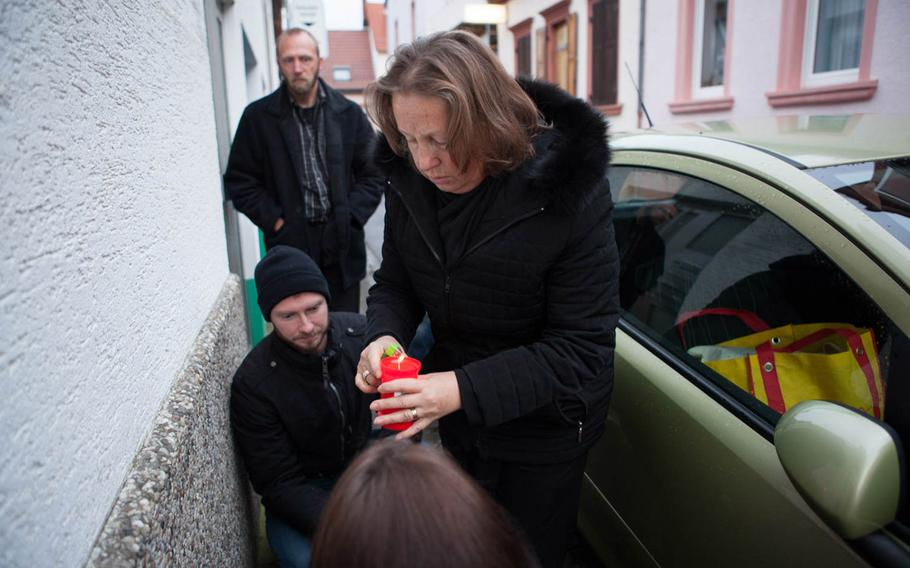 Eugenia Bushmich, the mother of Petty Officer 2nd Class Dmitry Chepusov, lights a candle on Jan. 30, 2015, outside of the building in Kaiserslautern, Germany, where her son was killed by a colleague in December 2013.