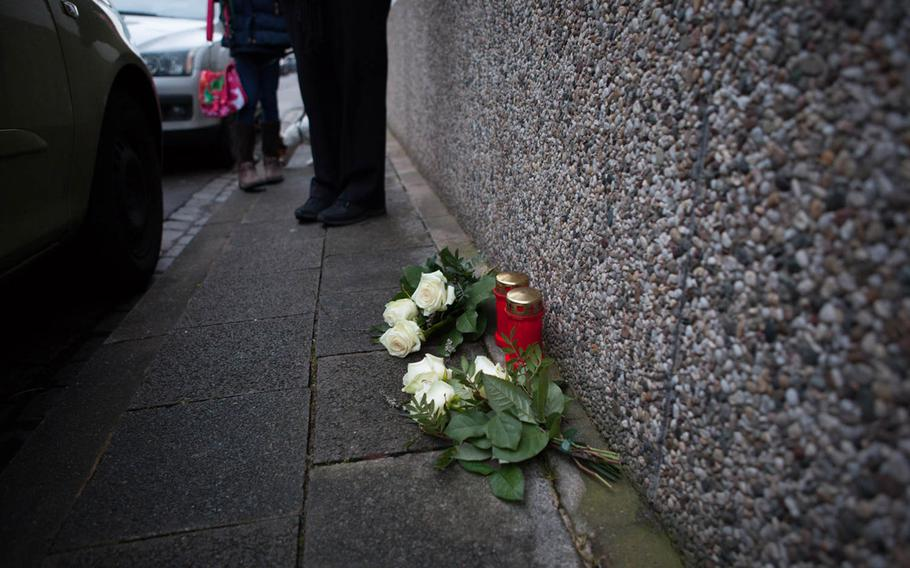 The family of Petty Officer 2nd Class Dmitry Chepusov placed candles and flowers on the sidewalk outside the apartment building in Kaiserslautern, Germany, where the sailor was killed in December 2013.