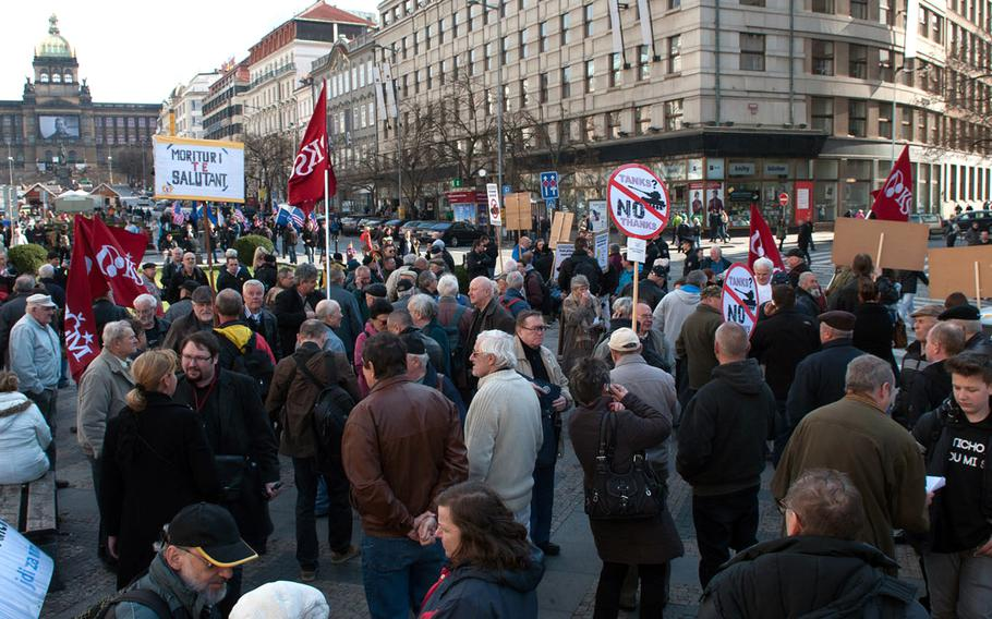 Activists protesting the U.S. Army's convoy operation through the Czech Republic gathered in Prague's Wenceslas Square, Saturday, March 28, 2015. Some carry red flags emblazoned with the logo of the Czech Communist Party.