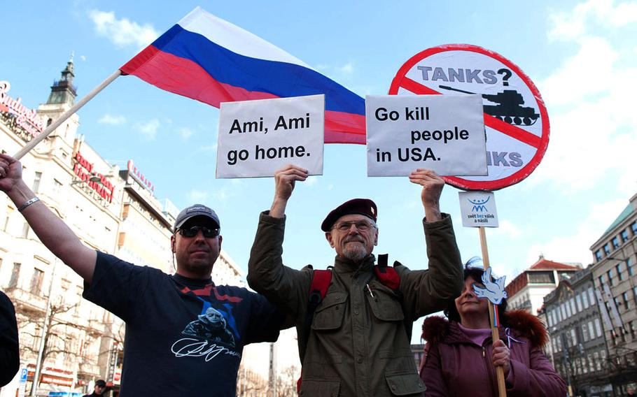 Protesters express their oppositiion to the crossing of a U.S. convoy through the Czech Republic during a demonstration in Prague on Saturday, March 28, 2015.