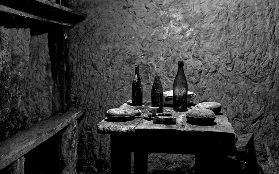 French soldiers' dining area underground with wine bottles, canteens and a serving dish. Photographed 6 December 2011. Vauquois, France.